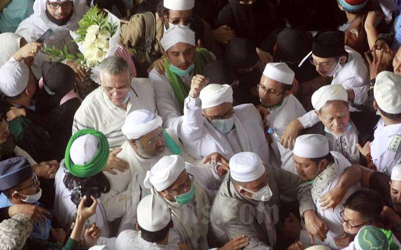 Habib Rizieq Shihab mengepalkan tangan setelah tiba di Bandara Soekarno Hatta,  Tangerang, Selasa (10/11/2020). Kedatangannya disambut oleh ribuan simpatisan dari berbagai daerah di Indonesia. Bisnis - Himawan L Nugraha