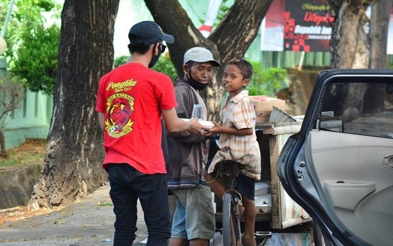 Komunitas pendukung PSM Makassar, The Macz Man berbagi makanan kepada pemulung di Makassar - Istimewa