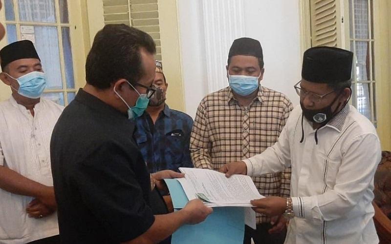 Ketua Tanfidziyah PCNU Kabupaten Cirebon KH Aziz Hakim Syaerozie (kanan), saat menyerahkan surat kepada Satgas Covid-19 kepada Bupati Cirebon, Imron Rosyadi. - Bisnis/Hakim Baihaqi