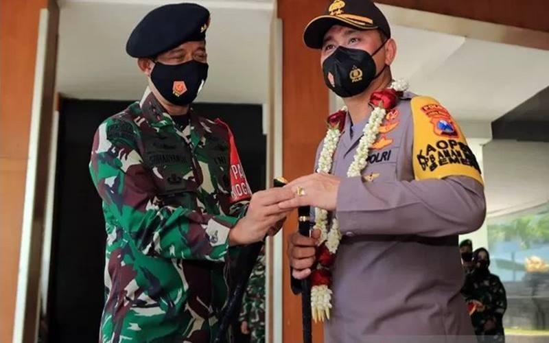 Pangdam V/Brawijaya Mayjen TNI Suharyanto (kiri) saat melepas Kapolda Jawa Timur Irjen Pol M Fadil Imran yang akan bertugas sebagai Kapolda Metro Jaya dengan penyematan cincin dan bunga di Makodam V/Brawijaya, Surabaya, Kamis (19/11/2020). - Antara