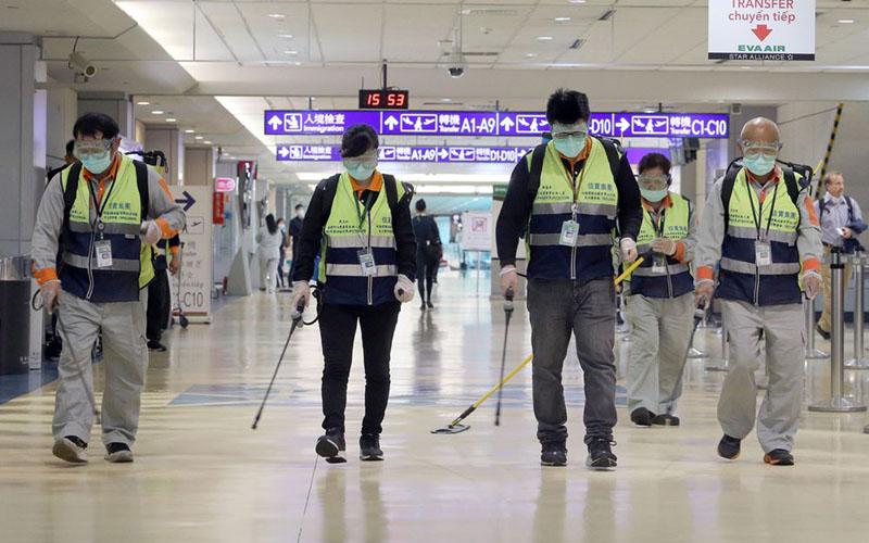 Petugas menyemprotkan disinfektan untuk membasmi vieus corona di Bandara Internasional Taoyuan di Taipei, Taiwan, pada 22 Januari 2020. - Bloomberg