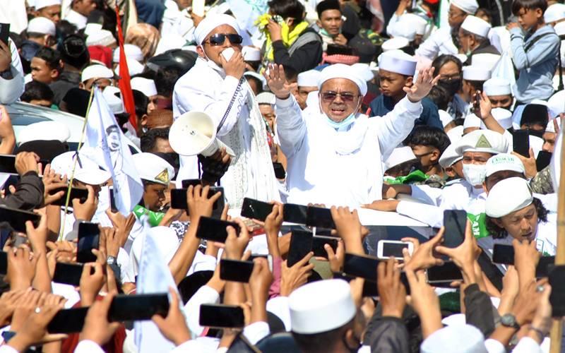 Imam Besar Habib Rizieq Shihab (tengah) menyapa ribuan jamaah di jalur Puncak, Simpang Gadog, Ciawi, Kabupaten Bogor, Jawa Barat, Jumat (13/11/2020) - Antara