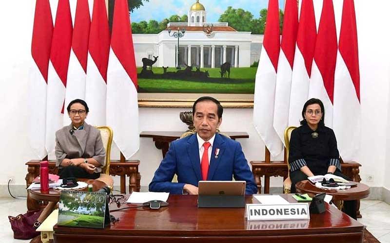 Presiden Joko Widodo (tengah) didampingi Menteri Luar Negeri Retno Marsudi (kiri) dan Menteri Keuangan Sri Mulyani Indrawati (kanan) saat mengikuti KTT Luar Biasa G20 secara virtual dari Istana Kepresidenan Bogor, Kamis (26/3/2020). - Biro Pers dan Media Istana