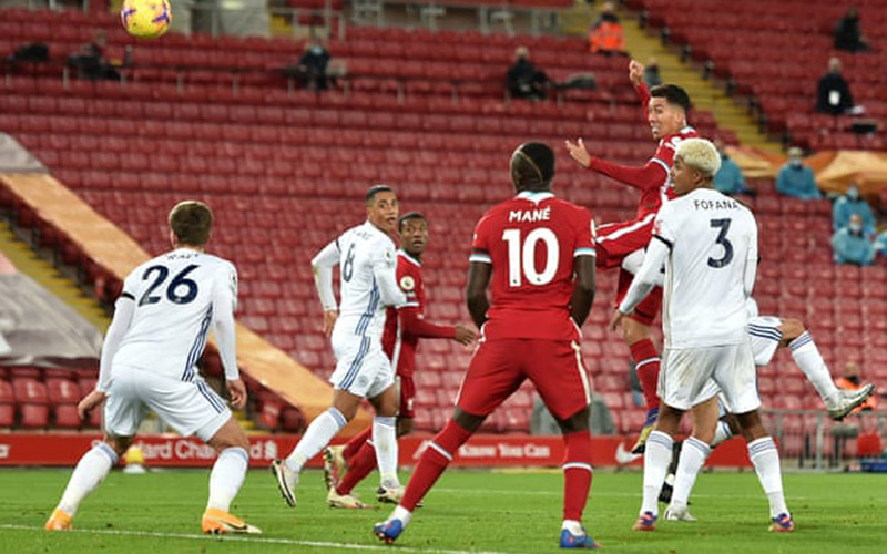 Penyerang Liverpool Roberto Firmino (kanan) menanduk bola untuk mencetak gol ketiga ke gawang Leicester City. - The Guardian