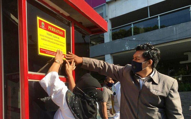 Petugas dari Bapenda Kota Malang Ade Herawanto memasang stiker pada Operasi Kepatuhan WP di Malang, Rabu (18/11/2020). - Istimewa
