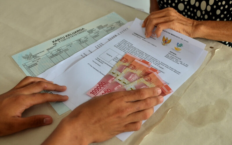 Petugas menyerahkan uang tunai saat penyaluran Bantuan Sosial Tunai (BST) tahap VIII di Kantor Kelurahan Ranoyapo, Amurang, Minahasa Selatan, Sulawesi Utara, Sabtu (7/11/2020). - Antara/Adwit B Pramono.