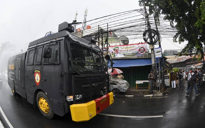 Sebuah kendaraan meriam air (water canon) menyemprotkan cairan disinfektan di kawasan Petamburan, Jakarta Pusat, Minggu (22/11/2020). Penyemprotan tersebut dilakukan menyusul adanya temuan kasus terkonfirmasi positif Covid-19 di kawasan Petamburan. - Antara