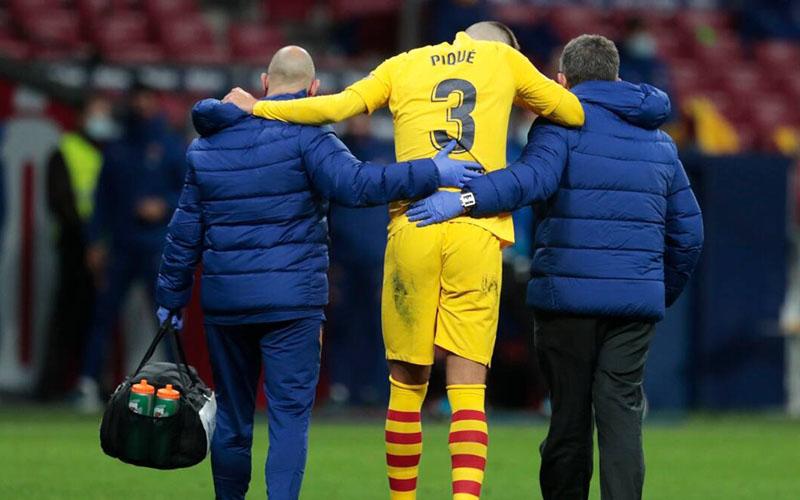 Bek Barcelona Gerard Pique tertati-tatih meninggalkan lapangan akibat cedera ketika timnya dikalahkan Atletico Madrid. - Sport