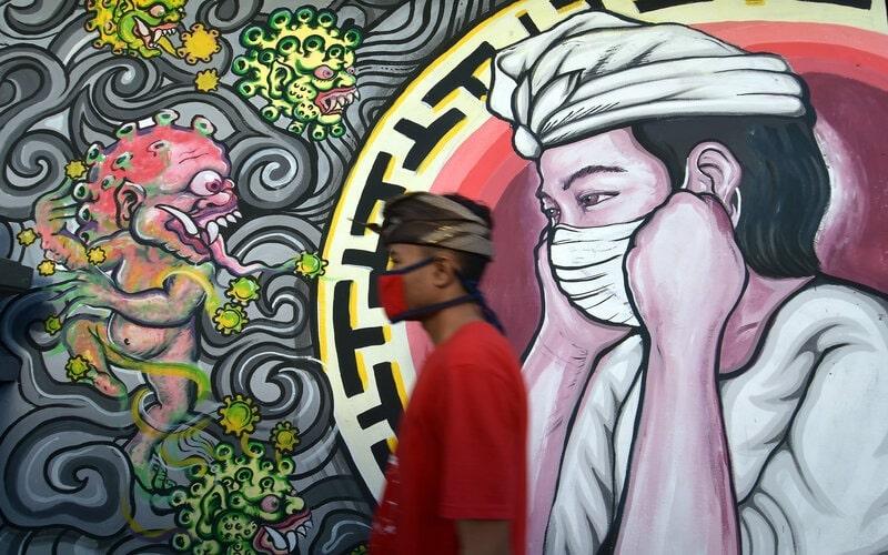 Warga melintas di dekat mural bergambar monster Covid-19 berhadapan dengan umat Hindu yang menggunakan masker di Denpasar, Bali, Senin (16/11/2020). - Antara/Nyoman Hendra Wibowo