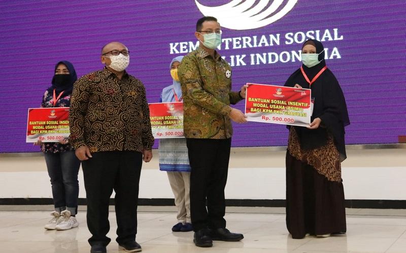 Menteri Sosial Juliari Batu Bara memberikan bantuan sosial insentif modal usaha bagi KPM PKH Graduasi sebesar Rp500 ribu  -  Sumber: Kementerian Sosial