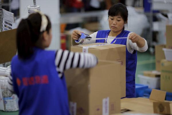 Karyawan Alibaba tengah mengemas barang pesanan pelanggan.  - Reuters