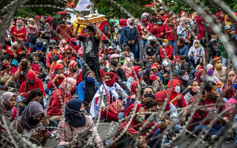 Massa berkerumun tanpa menjaga jarak fisik protokol kesehatan saat mengikuti aksi penolakan terhadap UU Cipta Kerja Omnibus Law di depan kompleks DPRD Jateng, Semarang, Jawa Tengah, Senin (12/10/2020). Satgas Penanganan Covid-19 mengimbau agar masyarakat yang berpartisipasi dalam menyampaikan aspirasi di depan publik melaksanakan protokol kesehatan dan menjaga jarak fisik guna mencegah penyebaran Covid-19 yang berpotensi terjadi pada kerumunan demonstrasi. ANTARA FOTO - Aji Styawan