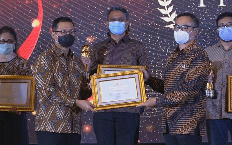 Menteri Sosial Juliari P. Batubara (kiri) menyerahkan plakat penghargaan Padmamitra bidang Disabilitas kepada anak usaha Bangkok Bank, PT. Bank Permata Tbk. (BNLI) yang diwakili oleh Head of Corporate Social Responsibility PermataBank, Hanggoro Seno (kanan), di Jakarta (17/11)  -  Siaran Pers Bank Permata