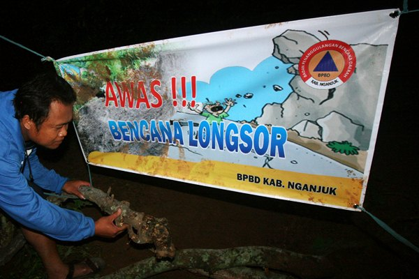 Warga memasang peringatan tanda bahaya di sekitar daerah longsor Dusun Dlopo, Desa Kepel, Kecamatan Ngetos, Nganjuk, Jawa Timur, Minggu (9/4). - Antara/Prasetia Fauzani