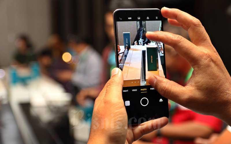 Pengunjung mencoba handphone OPPO Reno3 saat unboxing seri Reno3 di Jakarta, Senin (16/3/2020). Bisnis - Eusebio Chrysnamurti