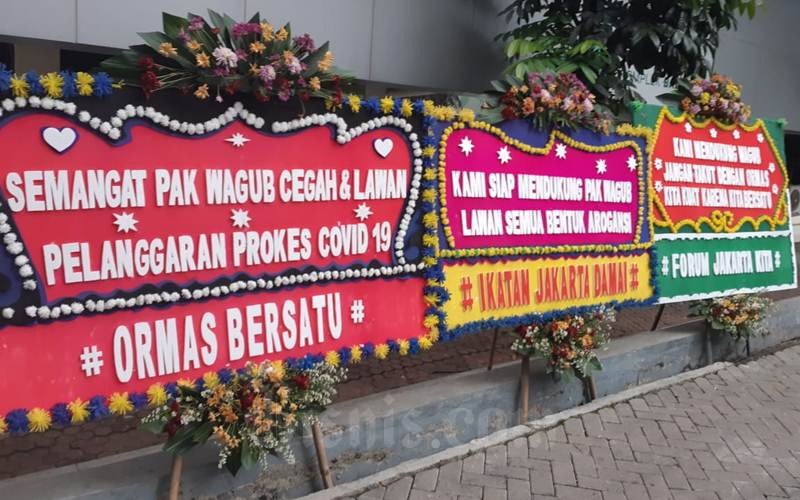 Karangan bunga berisi pesan dukungan kepada Wagub DKI untuk menegakkan hukum bagi pelanggar protokol kesehatan untuk mencegah Covid-19. - Bisnis/Nyoman Ari Wahyudi