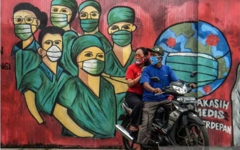 Ilustrasi - Pengendara motor melintas di depan mural tentang pandemi Covid-19 di Jalan Raya Jakarta-Bogor, Depok, Jawa Barat, Jumar (3/4/2020). - Antara