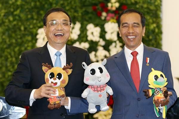 Presiden Joko Widodo (kanan) dan Perdana Menteri China Li Keqiang memegang maskot Asian Games 2018,  di Istana Kepresidenan Bogor, Senin (7/5/2018). - Reuters