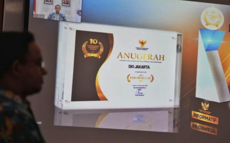 Gubernur DKI Anies Baswedan berfoto di depan anugerah yang diterima Pemprov DKI - Facebook/Anies Baswedan