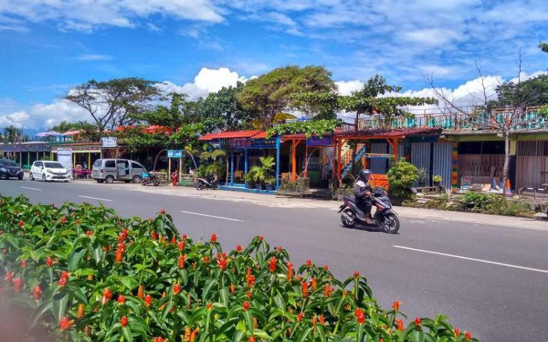 Seorang pengendara tengah melintasi kawasan wisata Pantai Padang, tempat yang paling populer dikunjungi wisatawan terutama di momen liburan akhir tahun. - Bisnis/Noli Hendra