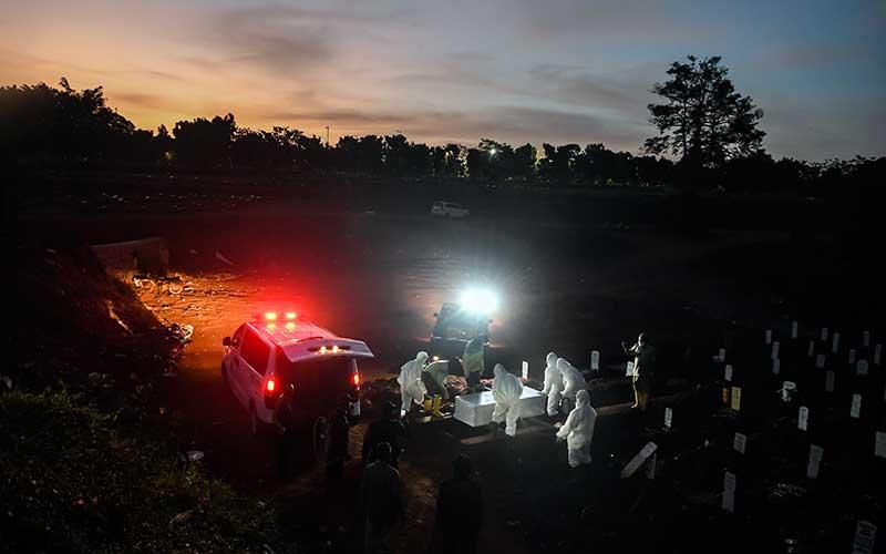 Petugas memakamkan jenazah Covid-19. - Antara/Muhammad Adimaja