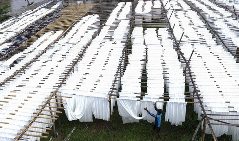 Pekerja menjemur kain rayon untuk bahan busana bermotif dan kain pantai di Mojolaban, Sukoharjo, Jawa Tengah, Kamis (2/1/2020). - ANTARA / Maulana Surya