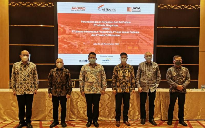 Djap Tet Fa Group CEO ASTRA Infra (keempat dari kiri) didampingi Kris Ade Sudiyono CEO Toll Road ASTRA Infra (ketiga dari kiri) berfoto bersama Gunung Kartiko Direktur Utama PT Jakarta Infrastruktur Propertindo (kedua dari kiri), Frans S. Sunito Direktur Utama Jakarta Toll Road Development (kelima dari kiri) pada acara Seremoni penandatanganan transaksi akuisisi 100% saham PT Jakarta Marga Jaya (JMJ) oleh ASTRA Infra. - Dok. Astra Infra