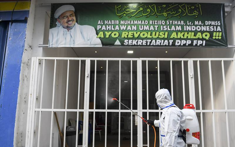 Anggota kepolisian dengan mengenakan hazmat menyemprotkan cairan disinfektan di kawasan Petamburan III, Jakarta Pusat, Minggu (22/11/2020). Penyemprotan tersebut dilakukan menyusul adanya temuan kasus terkonfirmasi positif Covid-19 di kawasan Petamburan. - Antara