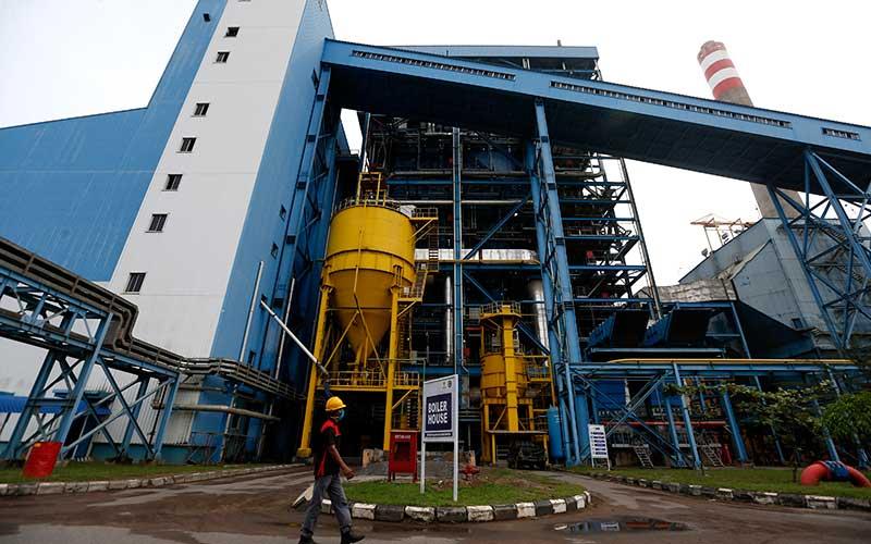 Pekerja melintas di depan tempat penguapan Pembangkit Listrik Tenaga Uap (PLTU) Nagan Raya,  di Nagan Raya, Aceh, Senin (28/9/2020). PLTU Nagan Raya memproduksi sekitar 220 Megawatt yang didistribusikan ke sejumlah unit transmisi untuk memenuhi kebutuhan energi listrik di seluruh Aceh. ANTARA FOTO - Irwansyah Putra