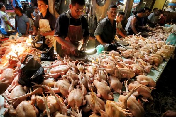Pedagang melayani pembeli ayam potong di pasar pagi Kota Lhokseumawe, Provinsi Aceh, Sabtu (4/6). - Antara