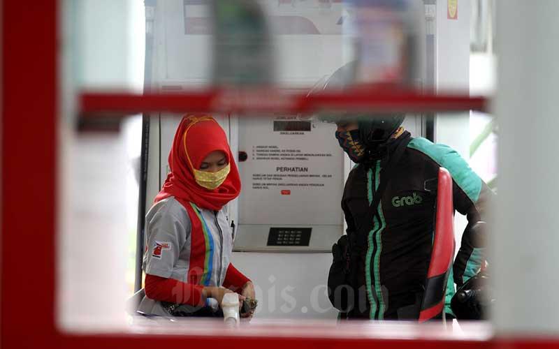Pengemudi ojek online mengisi BBM di salah satu stasiun pengisian bahan bakar umum (SPBU) di Jakarta, Selasa (14/4/2020). Pertamina meluncurkan layanan khusus untuk para ojol berupa cashback saldo LinkAja dengan maksimal nilai Rp15.000 per hari, untuk pembelian bahan bakar minyak (BBM) di SPBU Pertamina melalui aplikasi MyPertamina. Bisnis - Arief Hermawan P