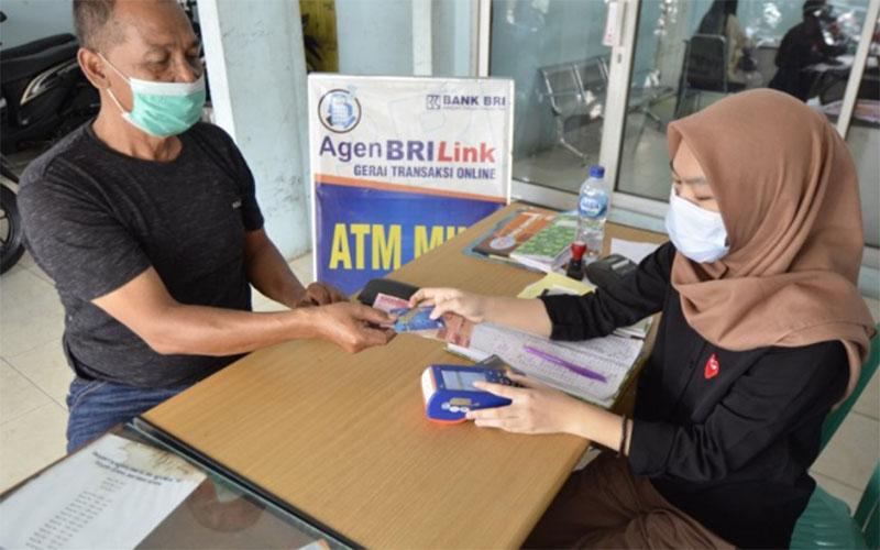 Seorang nasabah mengambil uang di agen BRILink yang berada di Way Halim, Bandar Lampung. - Antara