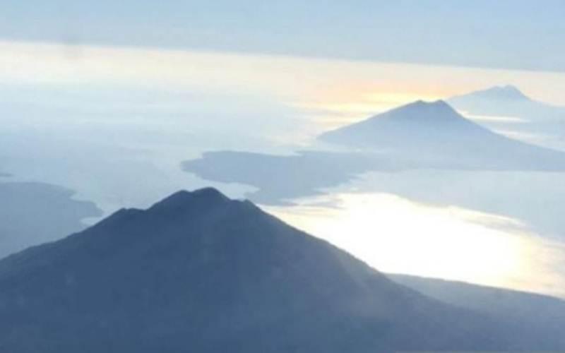 Gunung Ile Lewotolok (tengah) di Lembata berderet dengan Gunung Ile Boleng (depan) di Pulau Adonara, Flores Timur, NTT. Foto dari udara. - Antara/Bernadus Tokan