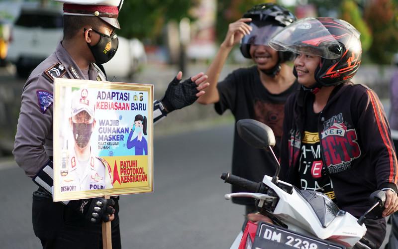 Anggota polisi lalu lintas memberikan imbauan mengenai protokol kesehatan kepada pengendara motor pada Operasi Zebra  - ANTARA