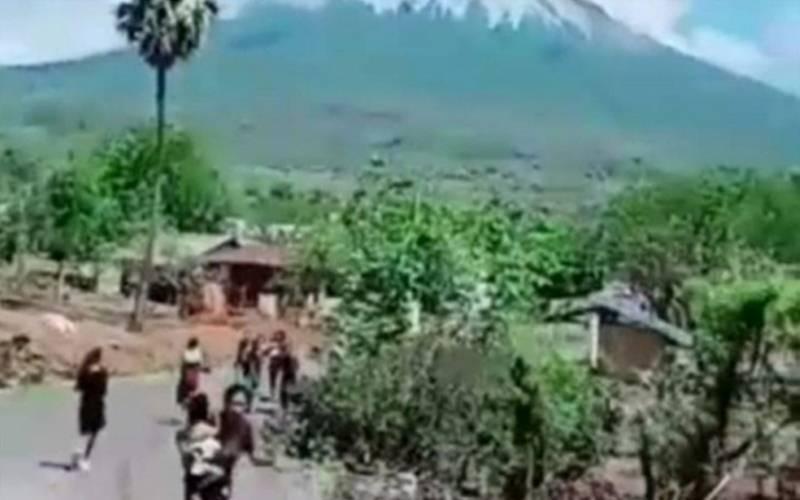 Seorang ibu tampak menggendong anaknya sambil berlari menyusul erupsi Gunung Ile Lewotolok, Kabupaten Lembata, Provinsi NTT, Minggu, (29/11/2020)./Antara - HO/Pemkab Lembata