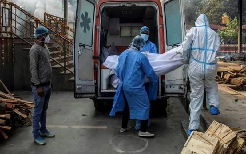 Tenaga kesehatan dan kerabat membawa jenazah seorang pria, yang meninggal dunia akibat penyakit  Covid-19 dari ambulans ke krematorium di New Delhi, India, Jumat (13/11/2020). - Antara/Reuters\r\n
