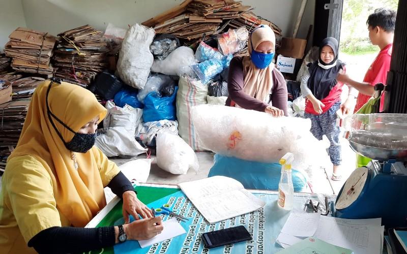 Petugas di Bank Sampah Padang tengah mencatat jumlah sampah yang dijual masyarakat dan menjadi tabungan emas dari PT Pegadaian Area Padang, Sumatra Barat. - Bisnis/Noli Hendra