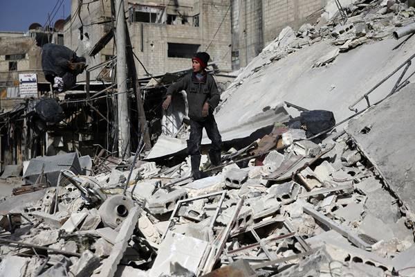 Seorang anak laki-laki berdiri di atas puing bangunan yang rusak di kota Douma yang terkepung, Ghouta Timur, Damaskus, Suriah, 5 Maret 2018. - Reuters