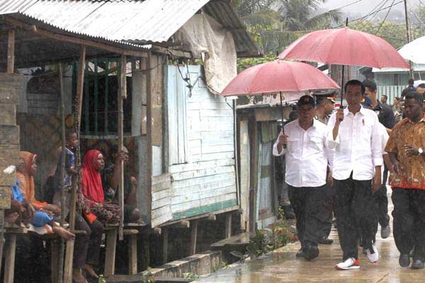 Presiden Joko Widodo (kedua kanan) didampingi Menteri PUPR Basuki Hadimuljono (kiri) mengunjungi pembangunan jalan program padat karya tunai di Kampung Kokoda, Distrik Sorong Manoi, Sorong, Papua Barat Jumat (13/4/2018). - Antara/Yulius Satria Wijaya