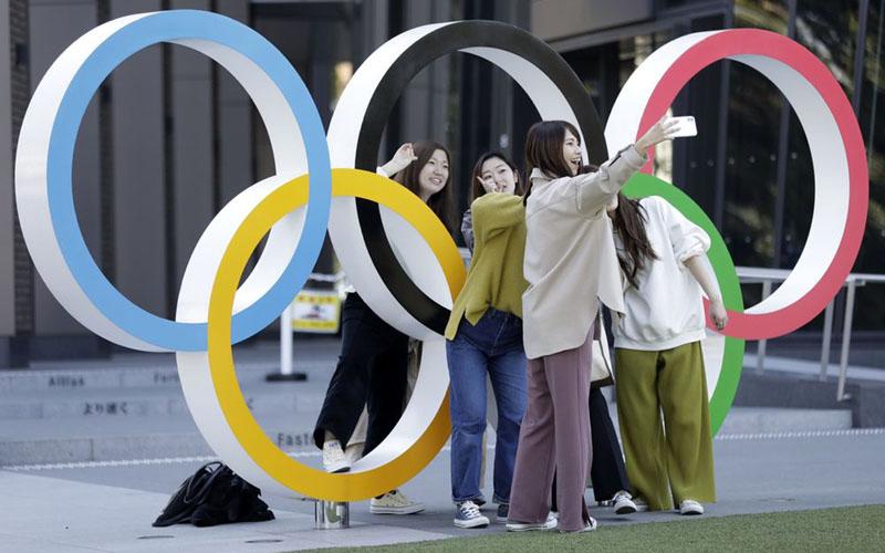 Sejumlah warga berfoto di dekat logo Olimpiade di depan Museum Olimpiade di Tokyo, Jepang, pada 11 Maret 2020./Bloomberg - Kiyoshi Ota