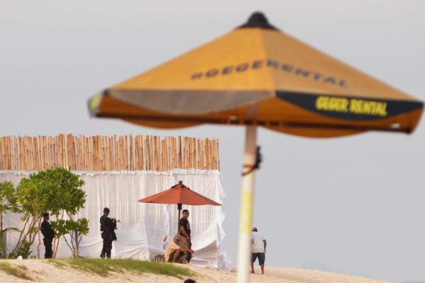Petugas melakukan pengamanan wilayah pantai yang ditutup dengan pagar bambu di kompleks Hotel St Regis, Nusa Dua, Bali, Senin (6/3). - Antara