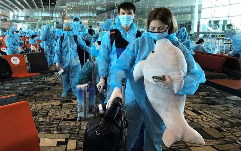 Seorang wanita Vietnam membawa boneka binatang saat akan naik penerbangan repatriasi dari Singapura menuju Vietnam di tengah penyebaran virus corona di Bandara Changi, Singapura, Jumat (7/8/2020)./ANTARA FOTO - REUTERS/Mai Nguyen/WSJ/djo