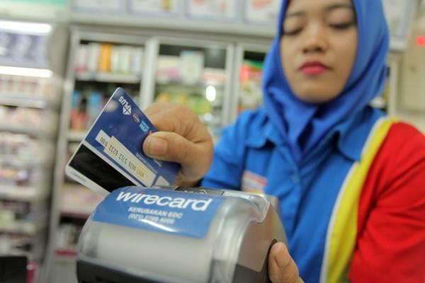 Karyawan minimarket menggesekan kartu debit di mesin Electronic Data Capture (EDC), di Jakarta, Selasa (5/9). Bank Indonesia melarang penggesekan ganda (double swipe) dalam transaksi nontunai dalam setiap transaksi. - ANTARA/Muhammad Adimaja