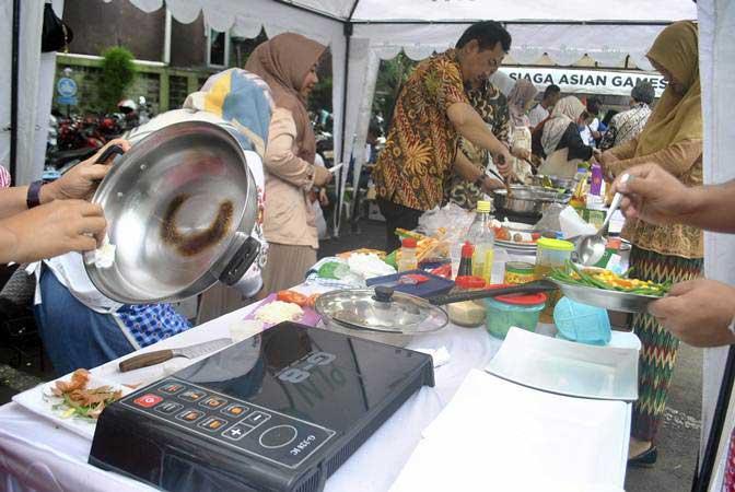 Sejumlah peserta memasak menggunakan kompor induksi di halaman kantor PLN UP3 Kota Bogor, Jawa Barat, Jum'at (15/2/2019). - ANTARA/Arif Firmansyah