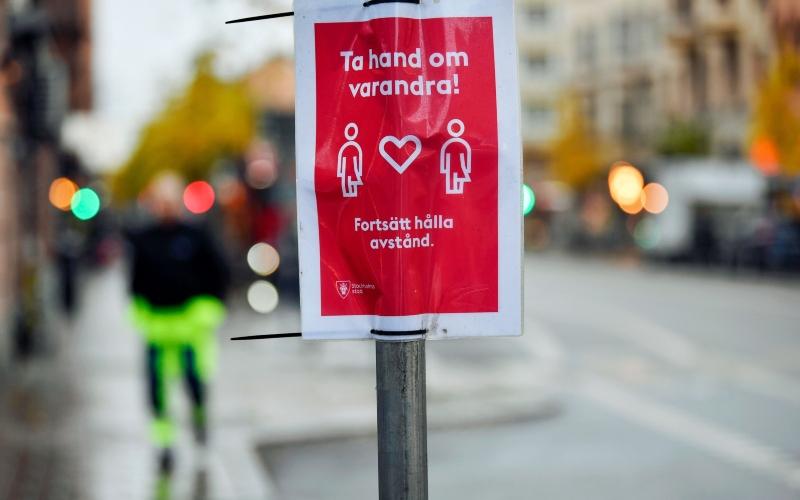 Poster yang meminta warga untuk saling menjaga kesehatan dan menjaga jarak dengan orang lain dipasang di tiang lampu di Stockholm, Swedia, Rabu (11/11/2020). - Bloomberg/Mikael Sjoberg