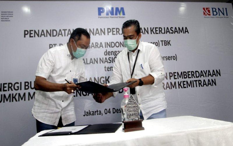 Direktur Bisnis UMKM BNI Muhammad Iqbal (kiri) dan Direktur Kepatuhan dan Manajemen Risiko PNM M. Q. Gunadi (kanan) menandatangani PKS tentang Sinergi BUMN Dalam Rangka Peningkatan Pemberdayaan UMKM Melalui Pengalihan Dana Program Kemitraan di Jakarta, Jumat (4 Desember 2020). Hingga saat ini, sudah lebih dari 10.000 debitur yang menerima manfaat penyaluran kredit hasil kerja sama antara BNI dan PNM.  - Dokumen BNI