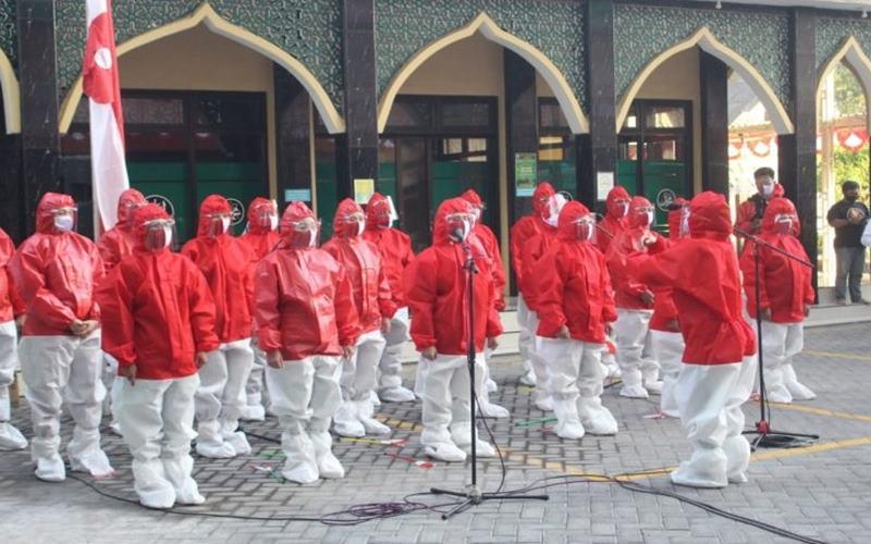 Tenaga medis di Rumah Sakit Islam Siti Hajar di Sidoarjo, Jawa Timur, mengenakan baju hazmat, masker, dan pelindung muka saat mengikuti upacara peringatan HUT RI pada Senin (17/8/2020). - Antara