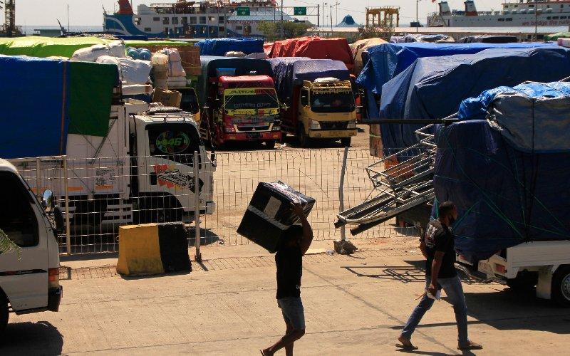 Sejumlah pria berjalan di antara truk pembawa logistik antarpulau di NTT di pelabuhan Angkutan Sungai, Danau dan Penyeberangan (ASDP) Indonesia Ferri di Bolok, Kupang, NTT (4/6/2020). Sebanyak 30 truk pengangkut logistik dan sembako ke sejumlah pulau di NTT tertahan di pelabuhan tersebut akibat pembatasan 50 persen kapasitas angkutan kapal guna mencegah penyebaran Covid-19.  - ANTARA