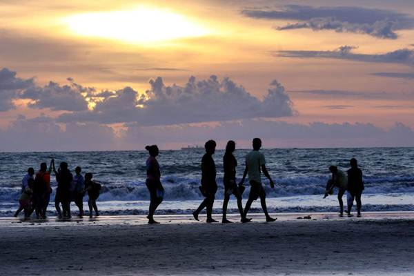 Wisatawan menikmati suasana matahari terbenam di Pantai Kuta, Bali, Selasa (20/3/2018). - JIBI/Rachman
