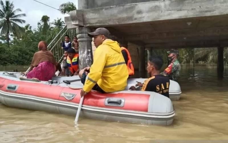 Tim BPBD mengevakuasi korban yang terjebak banjir di Aceh Timur Senin (7/12/2020). - Antara\r\n